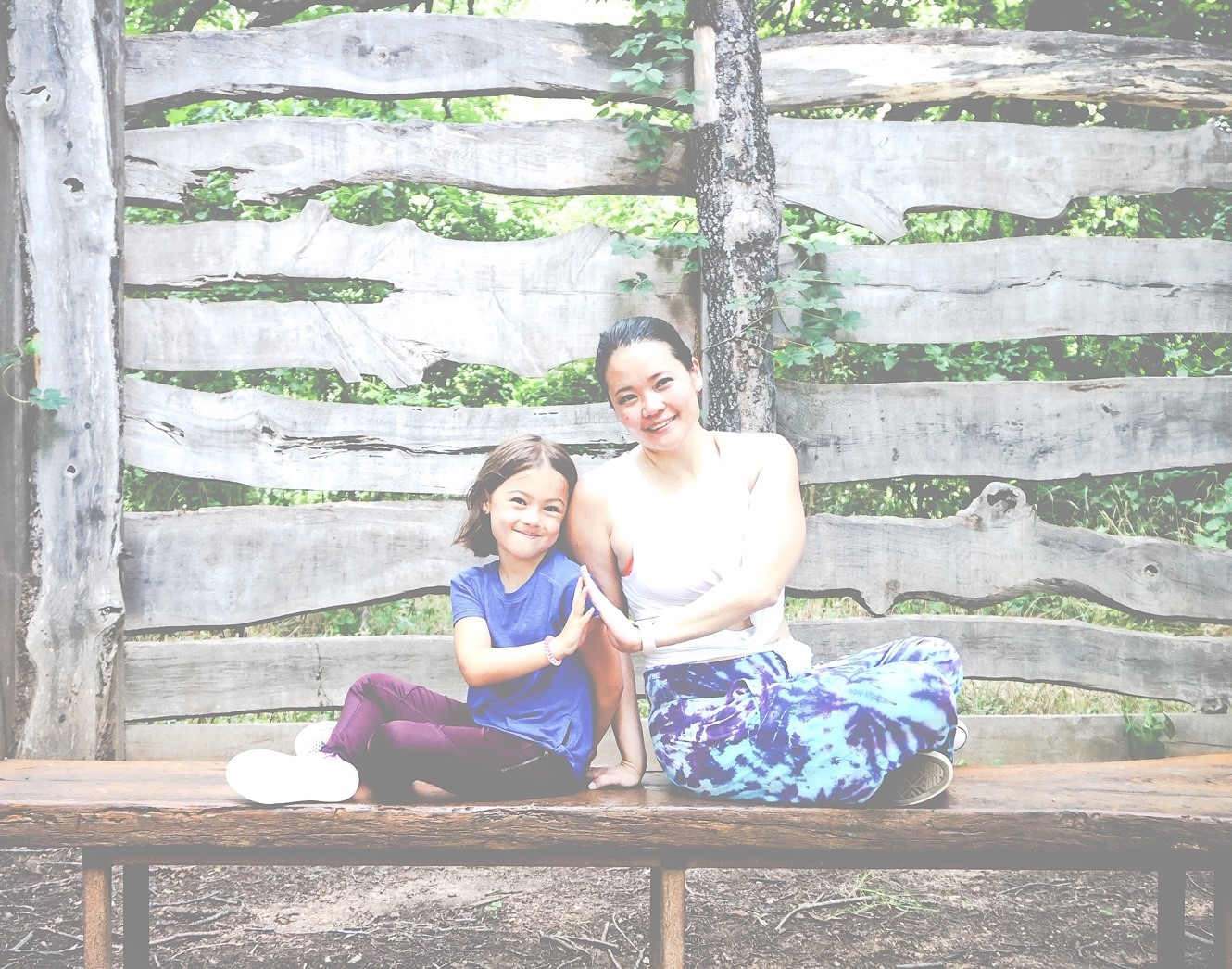 picture of owner and her daughter in a seated twist partner yoga pose.