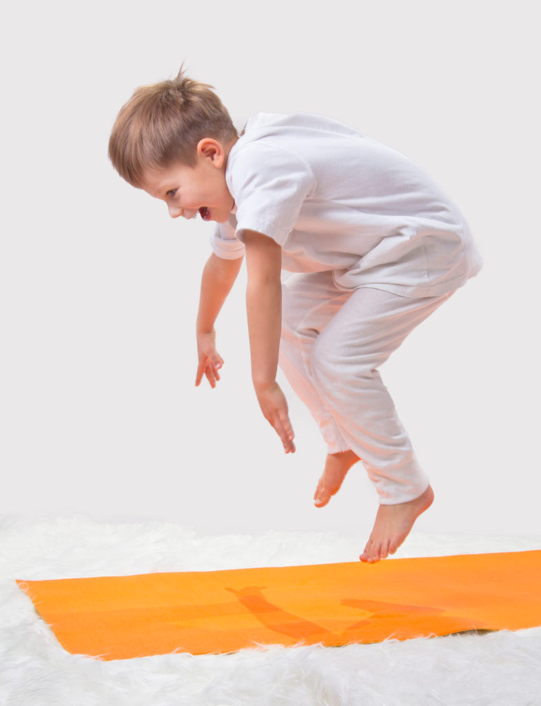 boy on an orange kids yoga mat, doing yoga for kids, jumping up in the air for frog pose.